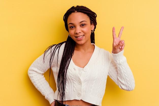 勝利のサインを示し、広く笑顔で黄色の壁に孤立した若いアフリカ系アメリカ人の女性。