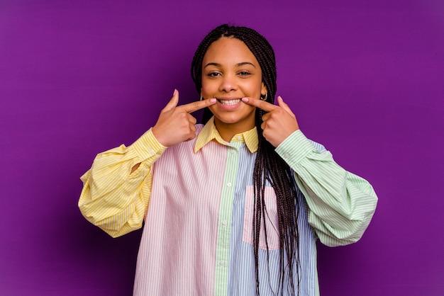 黄色の壁に孤立した若いアフリカ系アメリカ人女性の笑顔、口に指を指して