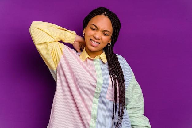 座りがちな生活のために首の痛みに苦しんでいる黄色の壁に孤立した若いアフリカ系アメリカ人の女性。