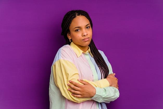 Молодая афро-американская женщина, изолированная на желтой стене подозрительно, неуверенно, исследует вас.