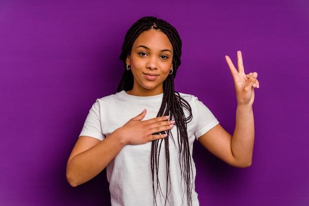 誓いを立てて、胸に手を置いて、黄色の壁に孤立した若いアフリカ系アメリカ人の女性。
