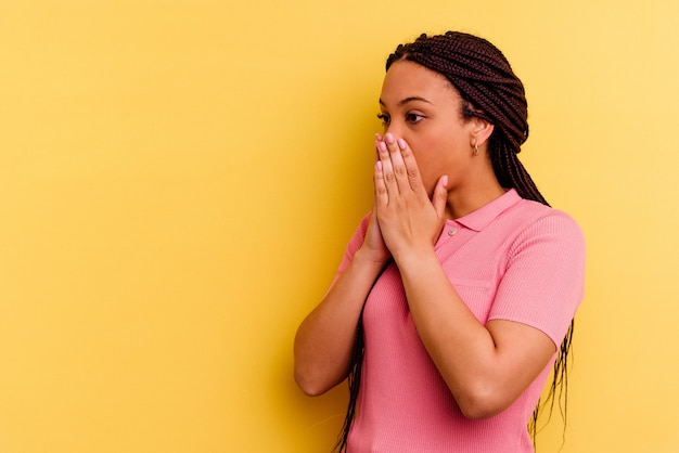 노란색 벽에 고립 된 젊은 아프리카 계 미국인 여자는 손으로 입을 덮고 복사 공간을 찾고 사려 깊은
