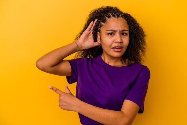 ゴシップを聴こうとしている黄色の壁に孤立した若いアフリカ系アメリカ人の女性。