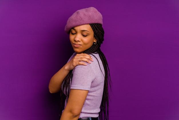 黄色い壁に隔離された若いアフリカ系アメリカ人女性肩の痛みを持っている黄色い壁に隔離された若いアフリカ系アメリカ人女性。