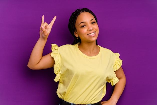 노란색 벽에 고립 된 젊은 아프리카 계 미국인 여자 혁명 개념으로 뿔 제스처를 보여주는 노란색 벽에 고립 된 젊은 아프리카 계 미국인 여자.