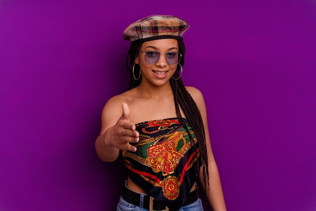 Молодая афро-американская женщина изолирована на желтой стене молодая афро-американская женщина изолирована на желтой стене, протягивая руку в жесте приветствия.