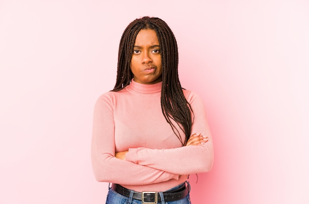 Young african american woman isolated on a pink background frowning face in displeasure, keeps arms folded.