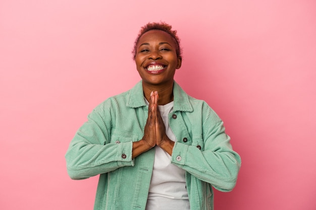 Young african american woman isolated on pink background holding hands in pray near mouth, feels confident.