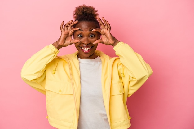 Young african american woman isolated on pink background keeping eyes opened to find a success opportunity.