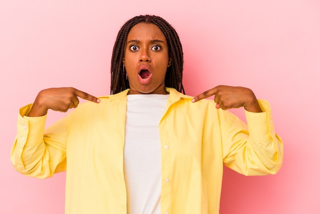 Young african american woman isolated on pink background  points down with fingers, positive feeling.