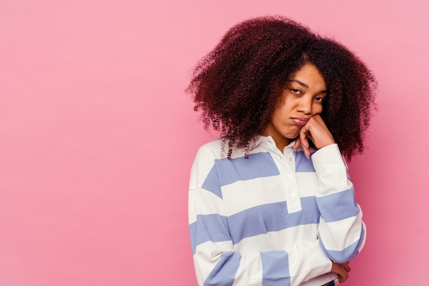 Young african american woman isolated on pink background who feels sad and pensive, looking at copy space.