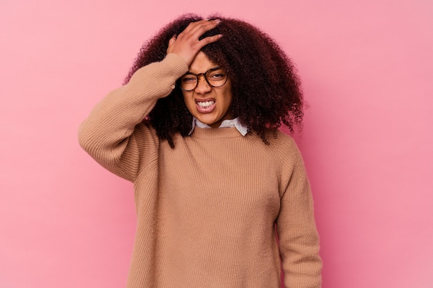 Young african american woman isolated on pink forgetting something, slapping forehead with palm and closing eyes.