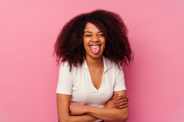 Young african american woman isolated on pink funny and friendly sticking out tongue.