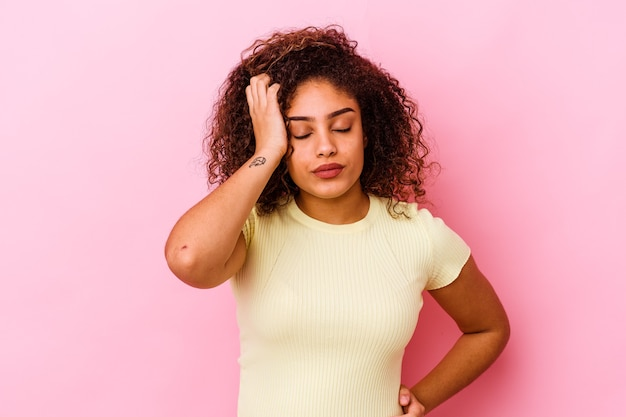 Young african american woman isolated on pink tired and very sleepy keeping hand on head.