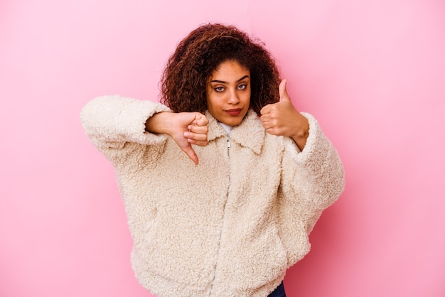 Young african american woman isolated on pink wall showing thumbs up and thumbs down, difficult choose concept