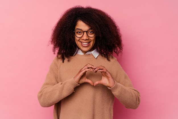 Young african american woman isolated on pink wall smiling and showing a heart shape with hands.
