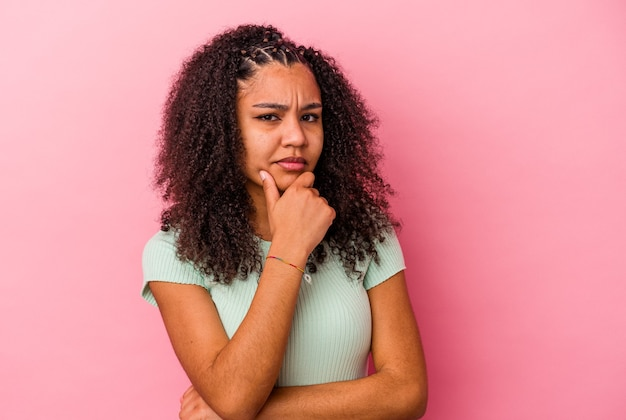 Young african american woman isolated on pink wall suspicious, uncertain, examining you.