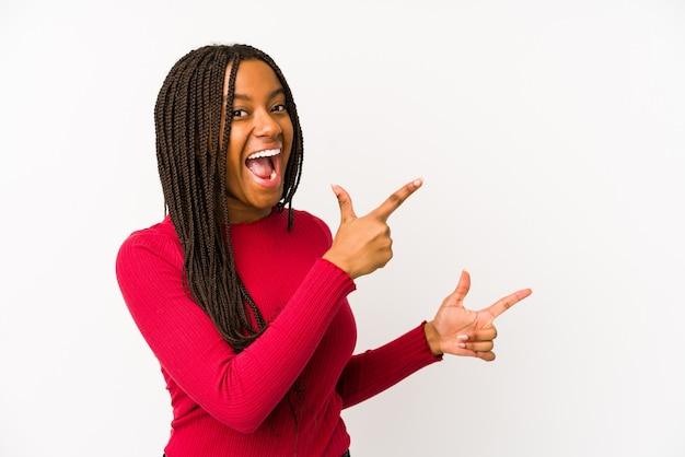 Молодая афро-американская женщина изолировала указывать с указательными пальцами к космосу экземпляра, выражая ободрение и желание.