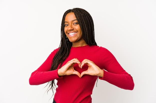 Молодая афро-американская женщина изолировала улыбку и показывала форму сердца руками.