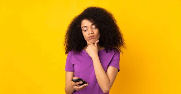 Young african american woman over isolated wall thinking and sending a message