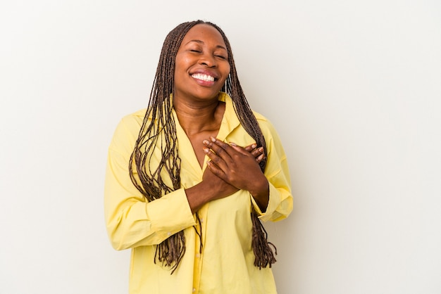 Young african american woman isolated on white background has friendly expression, pressing palm to chest. love concept.