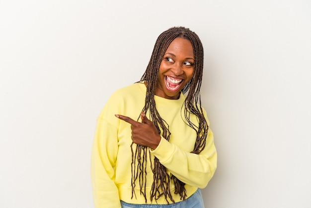 Young african american woman isolated on white background looks aside smiling, cheerful and pleasant.