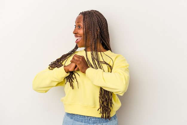 Young african american woman isolated on white background praying for luck, amazed and opening mouth looking to front.