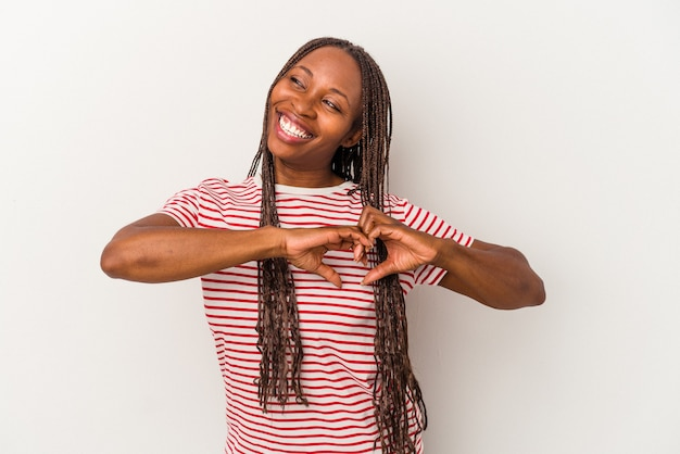 Young african american woman isolated on white background smiling and showing a heart shape with hands.
