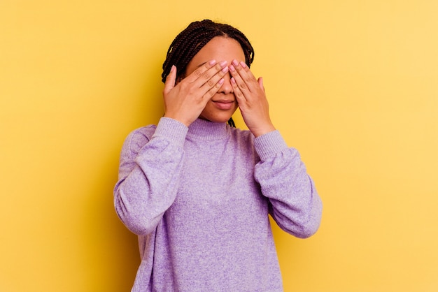Young african american woman isolated on yellow background afraid covering eyes with hands.