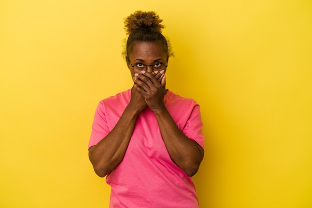 Young african american woman isolated on yellow background covering mouth with hands looking worried.