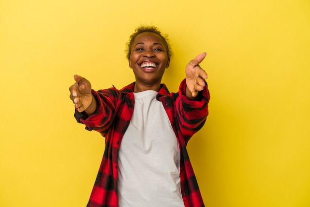 Young african american woman isolated on yellow background feels confident giving a hug to the camera.