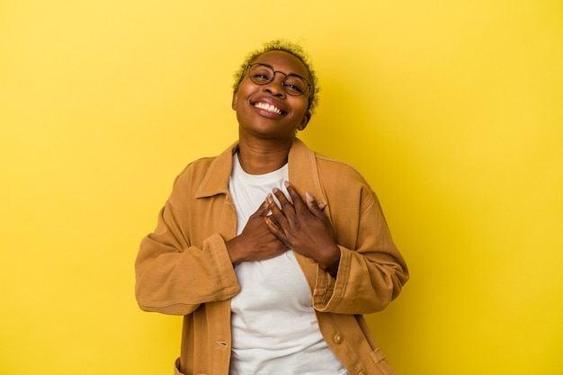 Young african american woman isolated on yellow background has friendly expression, pressing palm to chest. love concept.