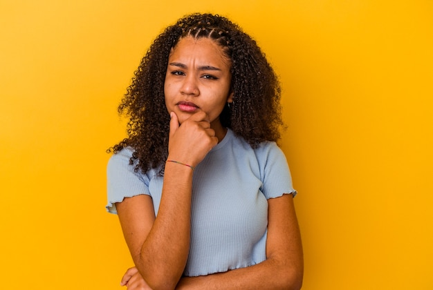 Young african american woman isolated on yellow background suspicious, uncertain, examining you.