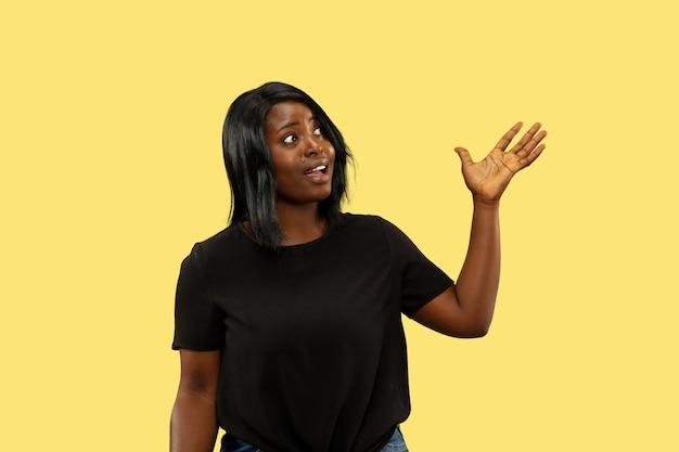 Giovane donna afro-americana isolata su giallo, espressione facciale