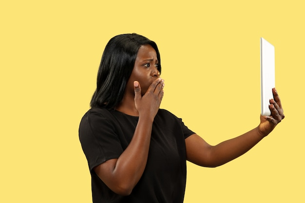 Young african-american woman isolated on yellow  space, facial expression. beautiful female portrait.