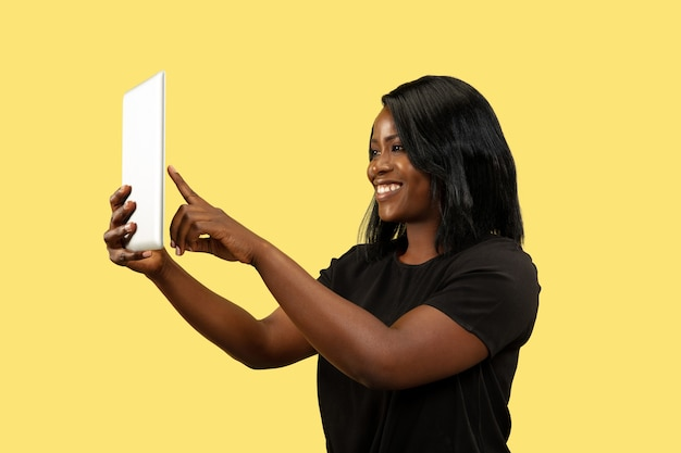Young african-american woman isolated on yellow studio background, facial expression. beautiful female portrait. concept of human emotions, facial expression. using tablet for selfie or vlog.