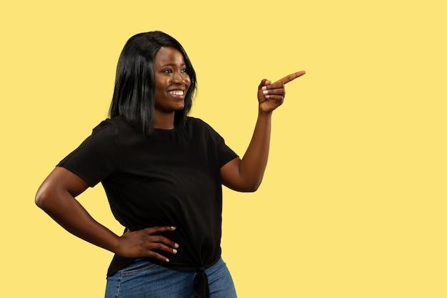 Giovane donna afro-americana isolata sulla parete gialla, espressione facciale. bellissimo ritratto femminile a mezzo busto. concetto di emozioni umane, espressione facciale. indicare e sorridere.