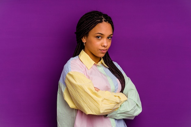 Young african american woman isolated on yellow wall frowning face in displeasure, keeps arms folded.
