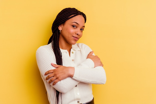 Young african american woman isolated on yellow wall hugs, smiling carefree and happy.