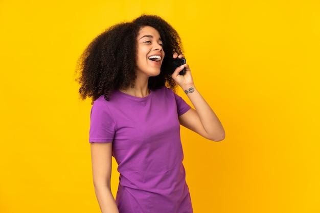 携帯電話との会話を維持する若いアフリカ系アメリカ人女性
