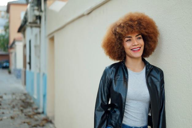 通りの壁にもたれて若いアフリカ系アメリカ人女性