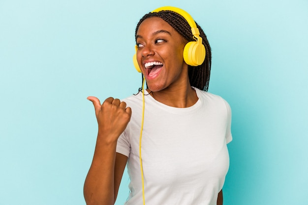Young african american woman listening to music isolated on blue background  points with thumb finger away, laughing and carefree.