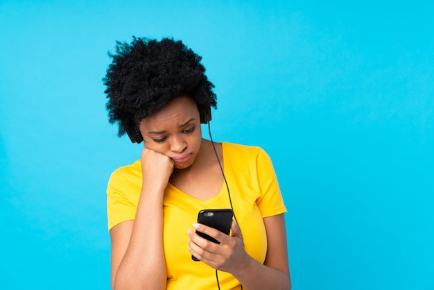 Young african american woman listening music with a mobile over isolated blue wall