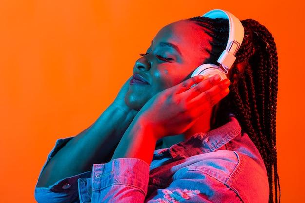네온 불빛에 헤드폰에서 음악을 듣고 젊은 아프리카 계 미국인 여자. 여성 초상화