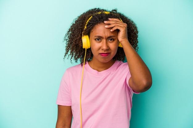 ショックを受けている青い背景に分離された音楽を聞いている若いアフリカ系アメリカ人の女性、彼女は重要な会議を思い出しました。