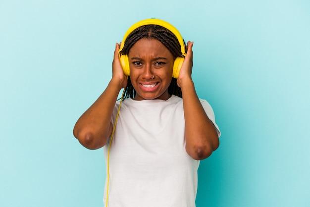 Молодая афро-американская женщина, слушающая музыку, изолирована на синем фоне, закрывая уши руками.