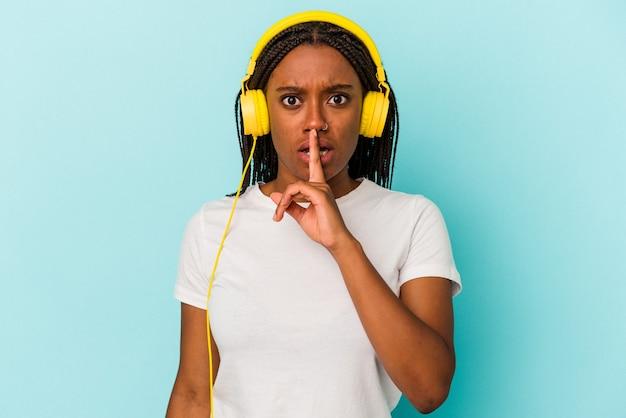 秘密を保持するか、沈黙を求めて青い背景で隔離の音楽を聞いている若いアフリカ系アメリカ人の女性。