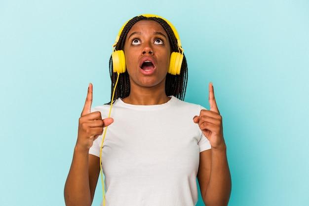 口を開けて逆さまを指している青い背景に分離された音楽を聞いている若いアフリカ系アメリカ人の女性。