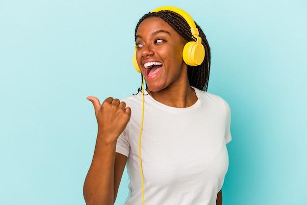 Молодая афро-американская женщина, слушающая музыку, изолированную на синем фоне, указывает пальцем, смеясь и беззаботно.
