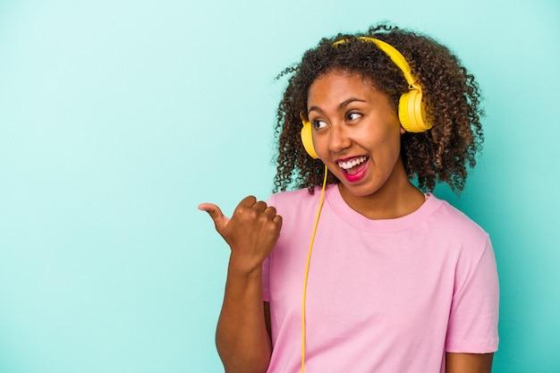 若いアフリカ系アメリカ人の女性は、親指の指を離れて、笑ってのんびりと青い背景のポイントで分離された音楽を聴いています。